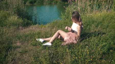 platform edge : Young woman relaxing on the river bank Stock Footage
