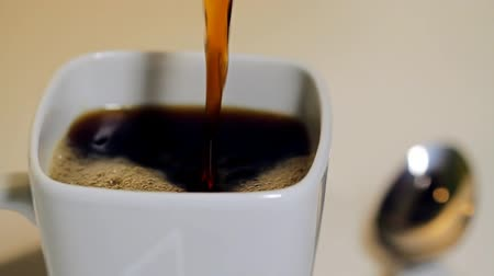black coffee : Coffee Pour Tilt Close Up. a close up tilting shot of coffee being poured into a white coffee mug. Shallow depth of field. silver spoon blurred in background Stock Footage
