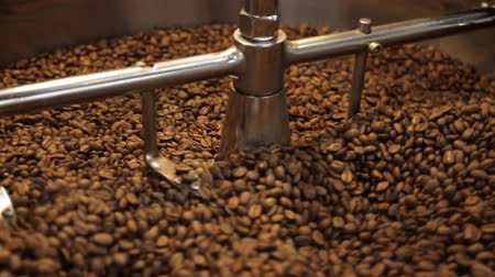 mennyiség : Coffee Bean Stir. Roasted coffee beans get sifted and stirred in an industrial machine. slow motion dolly left to right. Stock mozgókép