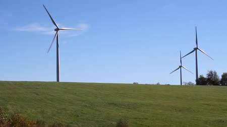 spřádání : Wind Turbines. 3 wind turbines spin in a field generating power