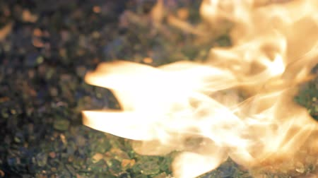 égés : Glass Close Up Fire. camera moves around and racks focus on glass shards on fire in gas fireplace Stock mozgókép