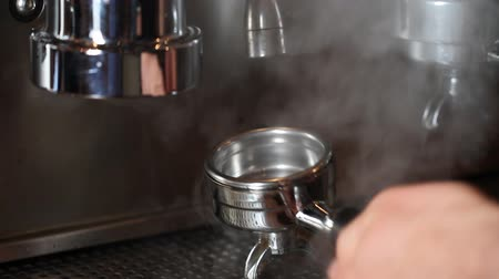 máquina : Cleaning Espresso Filter Medium. an employee cleans off and espresso filter with water and steam from the espresso machine Stock Footage