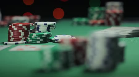 фокус : Poker Dolly Pot. 2 clips.  first is a left to right dolly shot. focus on center stack of the chips.  second shot is a dolly shot from right to left. focus on pile of poker chips in the center. chips are thrown in.  slow motion. shallow depth of field. Стоковые видеозаписи