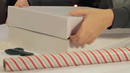 фокус : Gift Wrap Dolly. camera dollies to the right as someone places the top of a box on a gift and prepares for wrapping. slow motion.