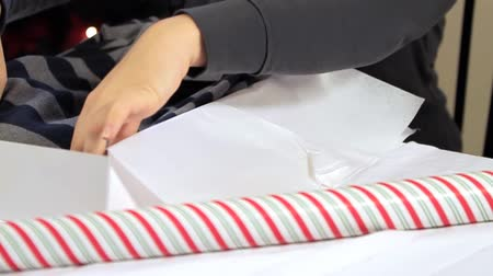 csomagolópapír : Boxing up a Shirt Bright. camera dollies to the left as person lays down shirt in gift box preparing for wrapping. slow motion Stock mozgókép