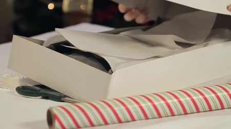 boŻe narodzenie : Boxing up a Shirt for Gift Wrapping. camera dollies left to right. slow motion. someone places top of box on the shirt and grabs wrapping paper. Christmas tree in the background.