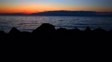 selektif : Back Lit Rocks at Sunset. focus on silhouette rocks during sunset on a lake.