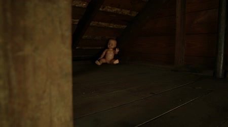 долл : Pumpkin Baby Attic Dolly. the camera tilts up and dollies right to reveal a baby doll sitting in the corner of an old attic. weird imagery for Halloween. Стоковые видеозаписи