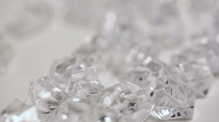 selektif : Clear Gems Slow Motion. camera slowly moves over a group of clear plastic gems on white gray background. macro, selective focus Stok Video