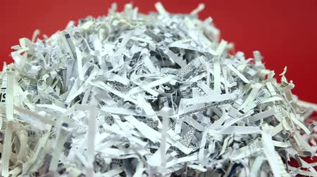 отходы : Shredded Paper Pan and Pull Back. 2 shots  first shot is a slow left to right pan around a stack of shredded business paper on a red background  second shot is a macro shot of shredded paper. camera pulls back slowly. shallow depth of field. Стоковые видеозаписи