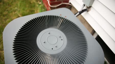 utilidade : Air Conditioner Unit Rise. camera moves away from a close up of the fan on top of an air conditioner unit outside next to a house