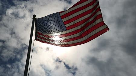 veterano : Backlit USA Flag by Sun. a flag wave against a backlit sun and blue sky and clouds