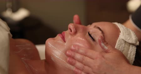 faíscas : Facial Cream Applied with Hands. camera slowly moves left as spa employee rubs facial cream on the clients face with her hands. close up.