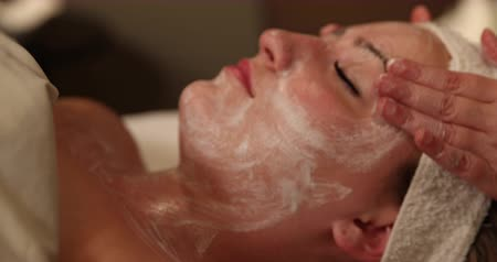 лицевой : Facial Rub Camera Pull Back. camera slowly pulls away from spa clients face receiving a facial treatment.