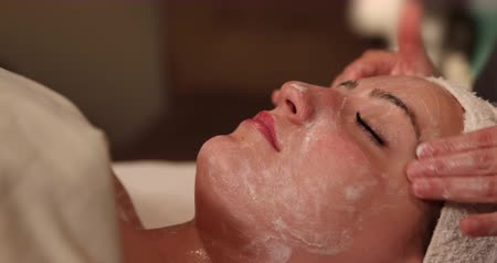 masaż twarzy : Rub Facial Cream on Face Dolly Right. camera moves right on close up of clients face as spa employee massages facial cream into her face. close up. Wideo