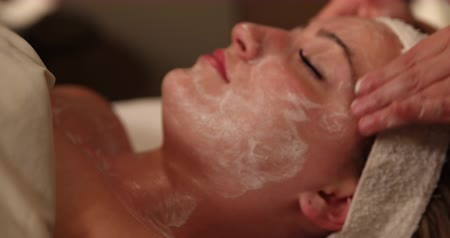 testa : Facial Massage Move In to Face. camera slowly moves into spa clients face receiving a facial massage. goes from out of focus to focus as camera moves in. close up. Stock Footage