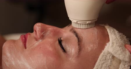 masaż twarzy : Facial Scrubbing Close Up. camera moves left as client receives exfoliating treatment on face. close up