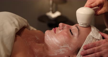 лицевой : Facial Scrubbing Medium Dolly. camera moves left as a spa client receives an exfoliating treatment.