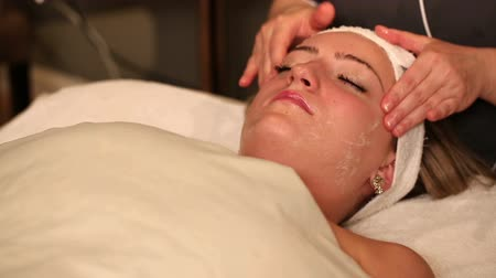 лицевой : Facial Treatment Rub Cream on Face. female spa client receives facial treatment. rubbing facial cream into face and forehead