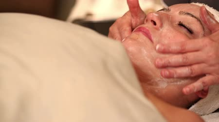masaż twarzy : Facial Treatment Rub in Cream. 2 shots. spa employee squirts facial lotion onto hand then camera tilts down to female clients face and rubs into face. 2nd clip is panning right to clients face receiving facial treatment.