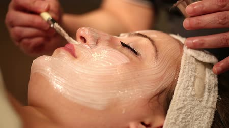 applying : Facial Treatment Close Up Head Tilt Down. camera moves down on close up of female spa clients face receiving a facial treatment. Stock Footage