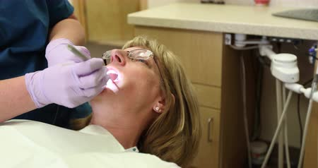 esquerda : Patient Receives Dental Exam. 2 shots. camera moves left on patient receiving dental oral exam. Then second shot is moving right on patient receiving dental exam. Stock Footage