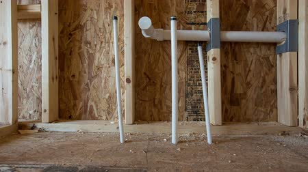 mozog e fel : PVC Piping for New Bathroom Construction Dolly. camera moves left on the future site of a bathroom vanity and sink. PVC pipes come up through the floor on this new under construction home Stock mozgókép