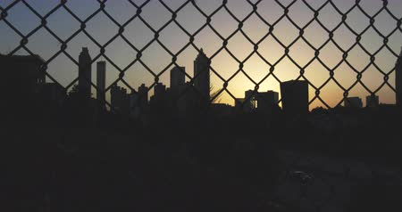 płot : Atlanta City Skyline Panning Right Behind Fence. camera pans right behind a chain link fence on the Atlanta City Skyline during sunset.