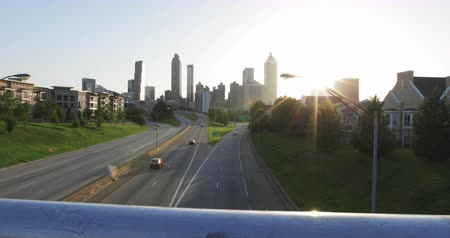 solar : Atlanta City Skyline Rise Above the Railing. the camera rises on a diagonal above the Jackson Street Guard Rails to show the sun flare coming from behind the buildings.
