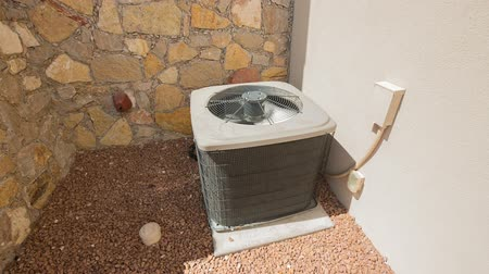 utilidade : AC Unit Rise and Lower on Stones. camera rises and descends on an air conditioning unit in an arid location. Placed on a stones against a stone and stucco facade Stock Footage