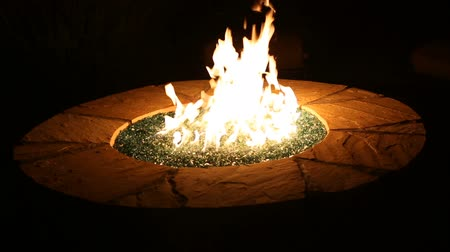 яма : Outdoor Burning Glass Fireplace Angle. shot of a roaring gas glass burning fireplace outdoors at night