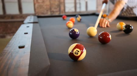 tiro : Pool Ball Hit in the Corner Pocket Lower. Two Shots. Camera lowers on player hitting the pool ball into the corner. One shot hits the ball in and next shot misses Stock Footage