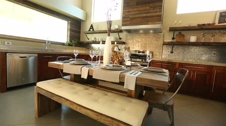 kabine : Wide Angle Dining Room Table in Kitchen Background. camera moves right on a wide angle shot of a modern dining room set surrounded by a contemporary industrial kitchen surrounding