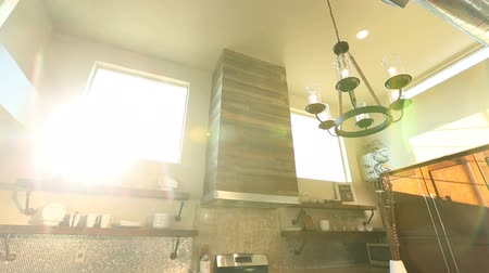 столовая : Tilt Up From Kitchen to Show Exposed Industrial Style Ceiling. camera tilts up from modern industrial style kitchen and dining room to ceiling, sun flare through window