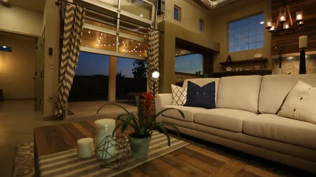 mozog e fel : Living Room Slow Move at Night with Door Open. camera slowly moves toward the sofa in this modern industrial style home while a garage type door opens to reveal the backyard