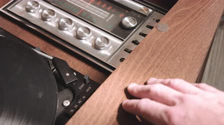 esquerda : Open Old Record Player and Auto Start. camera pans left as a person opens an old record player, turns on and places record on turntable, then presses the auto start lever to begin playing the record