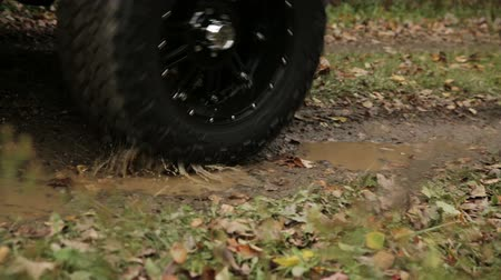 bahno : Truck Drives Through Mud Puddle Rack Focus. camera moves right as truck drives through mud puddle with tires and rack focus to grass in foreground