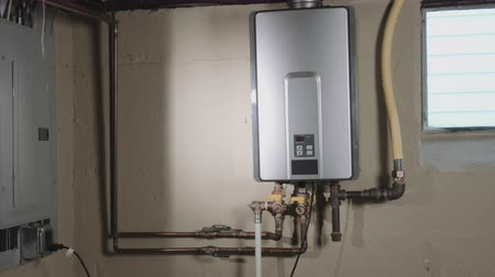 grzejnik : Closeup Reveal Tankless Water Heater From Behind Wall. camera moves left from behind a wall to reveal a tankless water heater on the wall in a basement