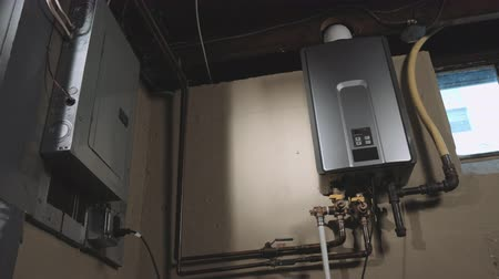 égés : Tankless Water Heater Tilt Up. a wide shot of the corner of a basement with an electrical box and a tankless water heater on the wall