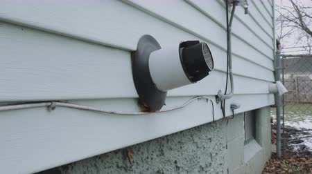 esquerda : Wide Panning Water Heater Vent Side of House. camera moves right and left on a wide shot of the side of the house showing a tankless water heater vent Stock Footage