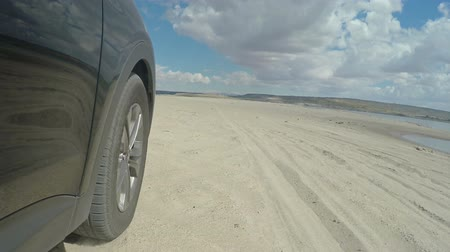 arka görünüm : Tire View Driving Through Sand Beach. car driving on the beach during summer time. Low angle view of the tire
