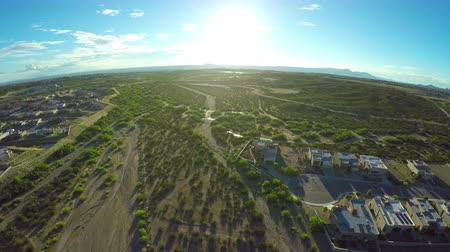 sociedade : Aerial View of Neighborhood in Desert with Sun Flare. an aerial view of the camera slowly moving towards sun over a neighborhood in the mountain range in the desert Stock Footage