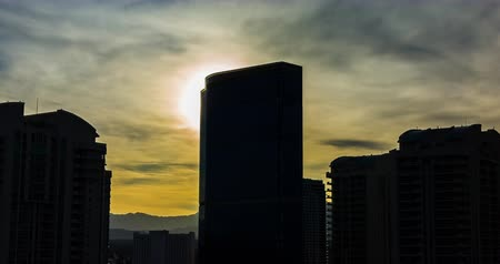 освещенный : Hotel Silhouette from Setting Sun Backlit Time Lapse. the sun sets behind a tall hotel in Las Vegas Nevada. Sun flare hits the corner of the hotel and silhouettes the skyline of buildings.