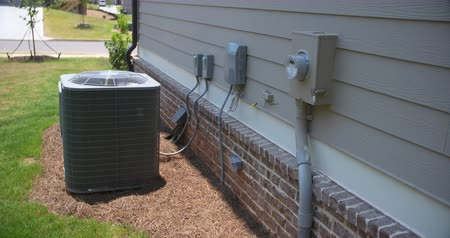 levegő : Air Conditioning Unit and Electric Meter Rise Side of Home. camera slowly rises on the side of a home showing the electric meter in the foreground and an central air conditioning unit in the background