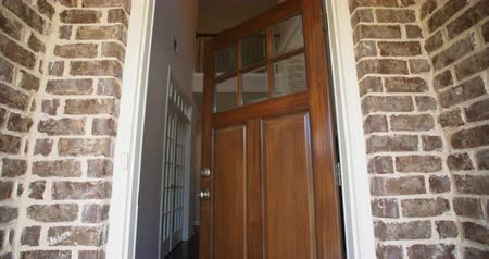 přední : Front Home Entrance Low Angle Door Open Rise Up. rising low angle shot of the front entrance as the door opens to reveal the hallway of a modern residential home