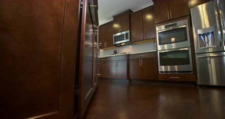 real : Kitchen Low Angle Reveal Appliances and Cabinets. camera slowly moves right to reveal kitchen from the island. Dark brown wood
