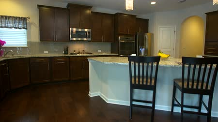 konyhai : Modern Kitchen Rise Up from Side. rising shot of a modern kitchen with granite island. Dark wood cabinets and flooring