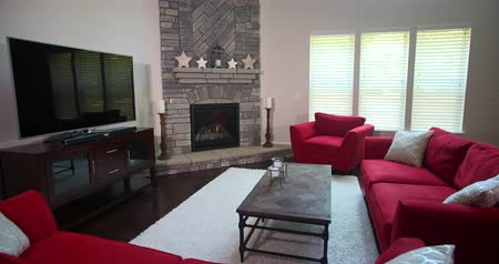 lareira : Modern Living Room Revealed from Behind Sofa. camera rises from behind a couch to reveal a modern furnished living room with red furniture, a fireplace, and entertainment console