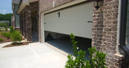 garagem : Home Garage Door Opens Angled Lowering. lowering shot on an angled front exterior of a new residential home as the garage door opens Vídeos