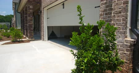 drzwi : Home Garage Door Closes Angled Rising. rising shot on an angled front exterior of a new residential home as the garage door closes